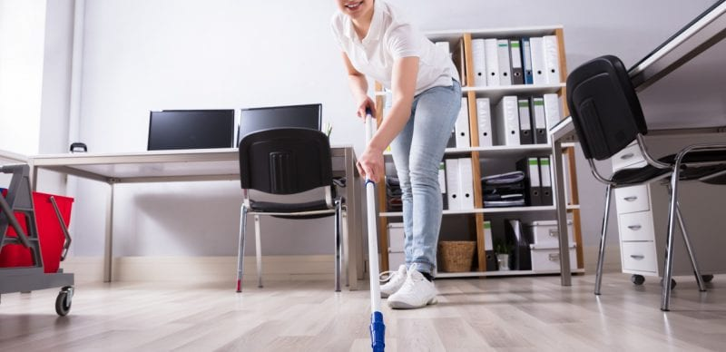 Female Janitor Cleaning Floor In Office
